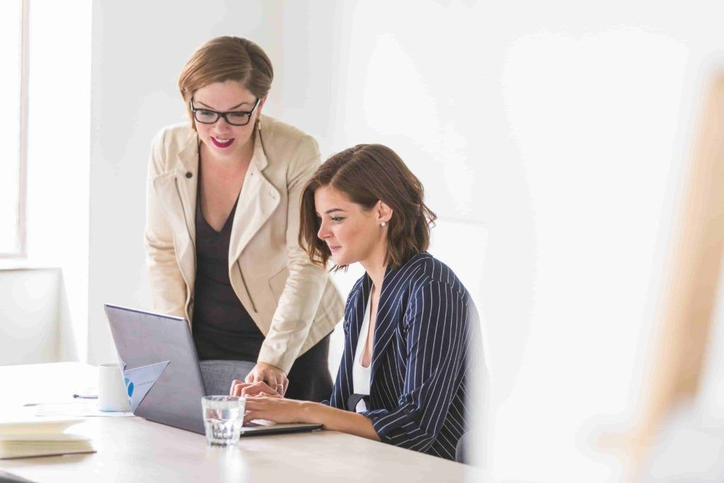 Two women, one seated, one standing, working at a laptop