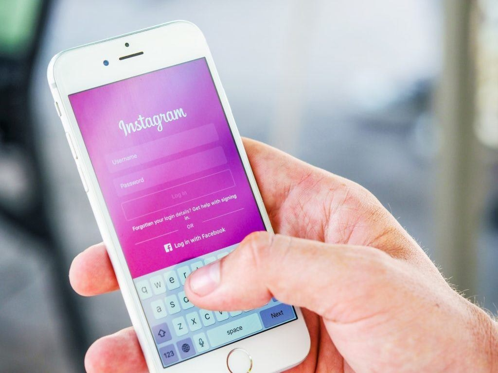 A hand holding an iphone with the Instagram login page displayed