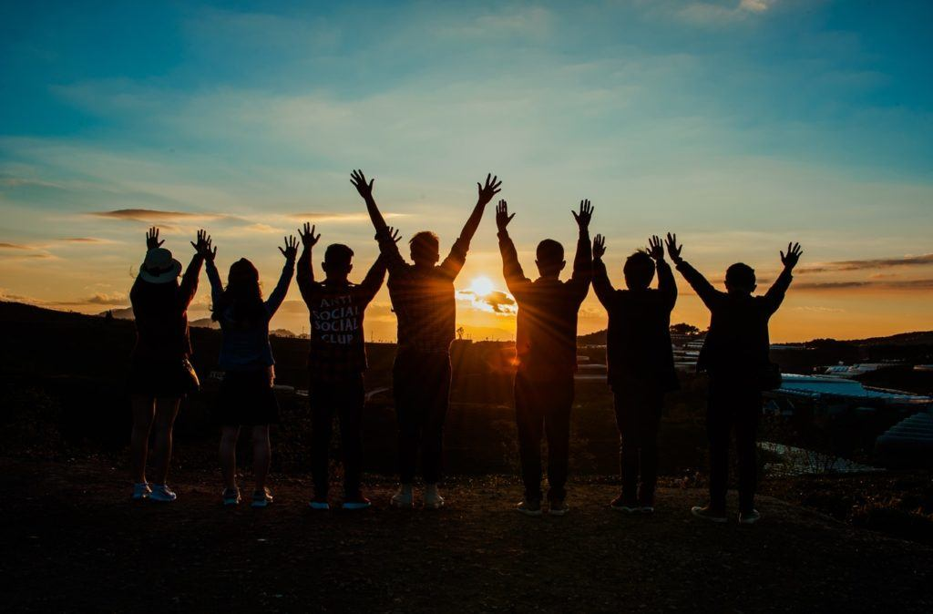 7 people stand silhouetted against a sunset