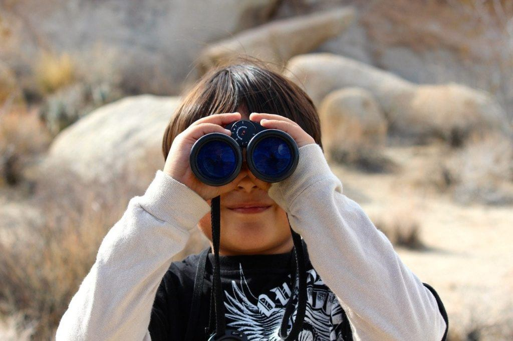 child peering through binoculars