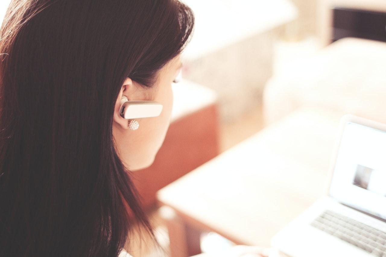 Frau mit Headset im Kundenservice als Remote Job