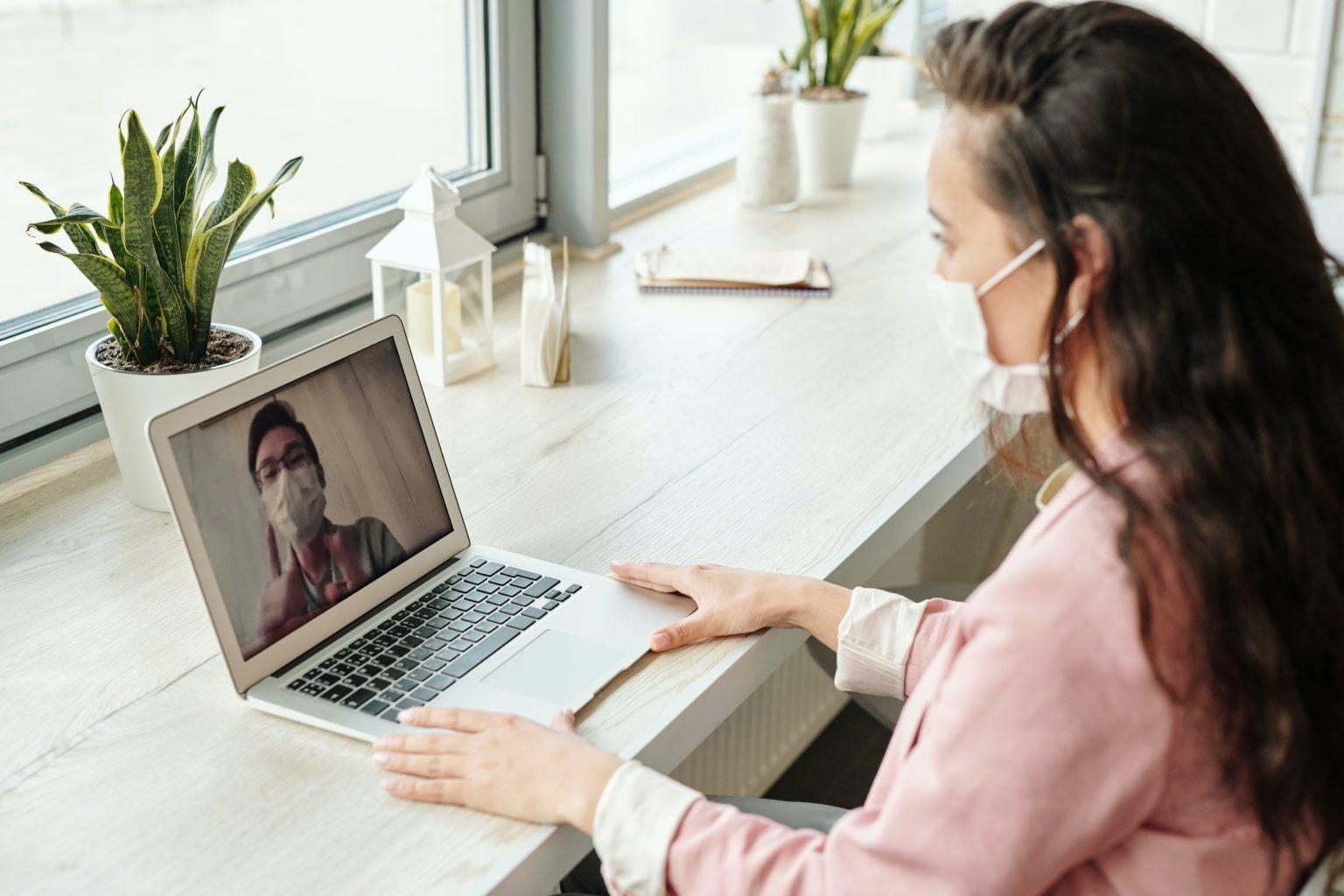 Frau in Videokonferenz mit Mundschutz