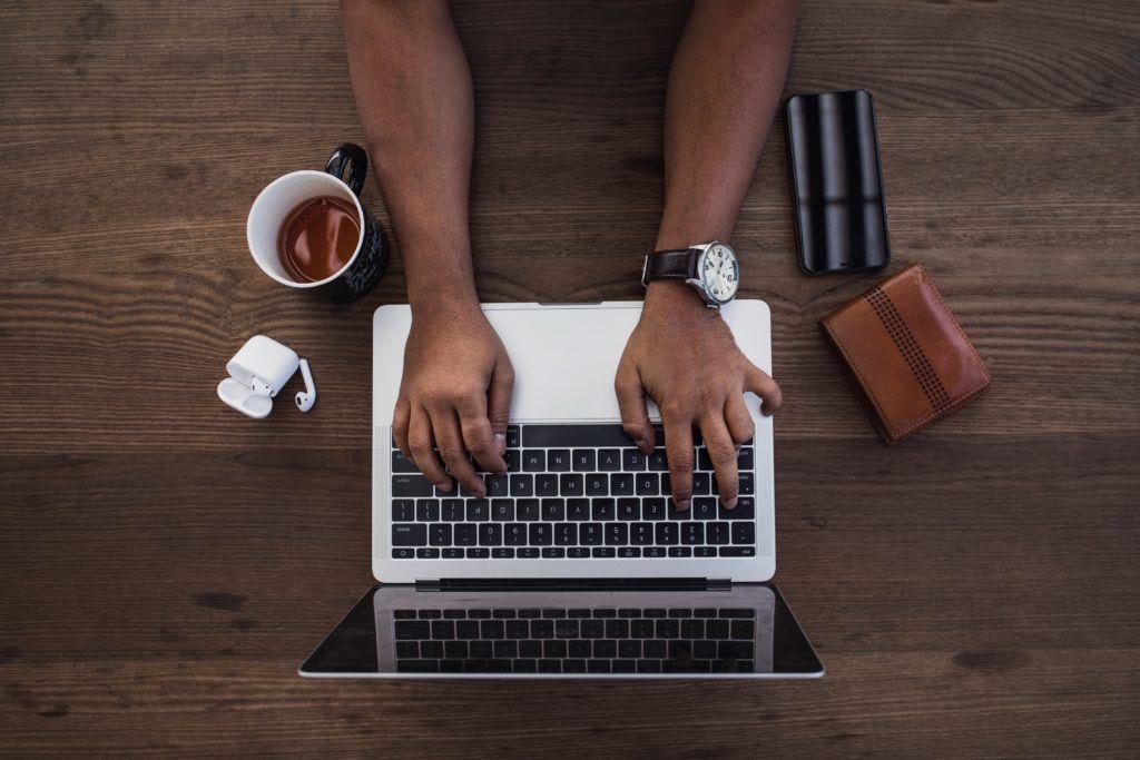 Hände über einem Laptop