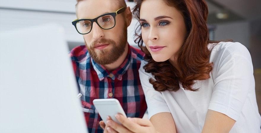 Frau und Mann am Computer mit Smartphone