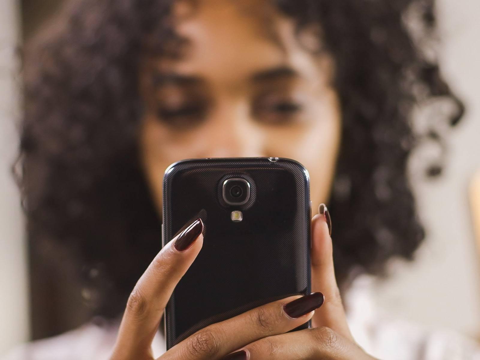 Mulher segura um smartphone e usa um editor de vídeo grátis