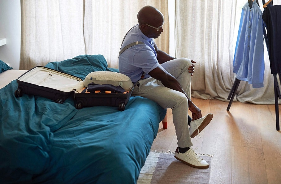 man sitting on edge of bed putting on shoe