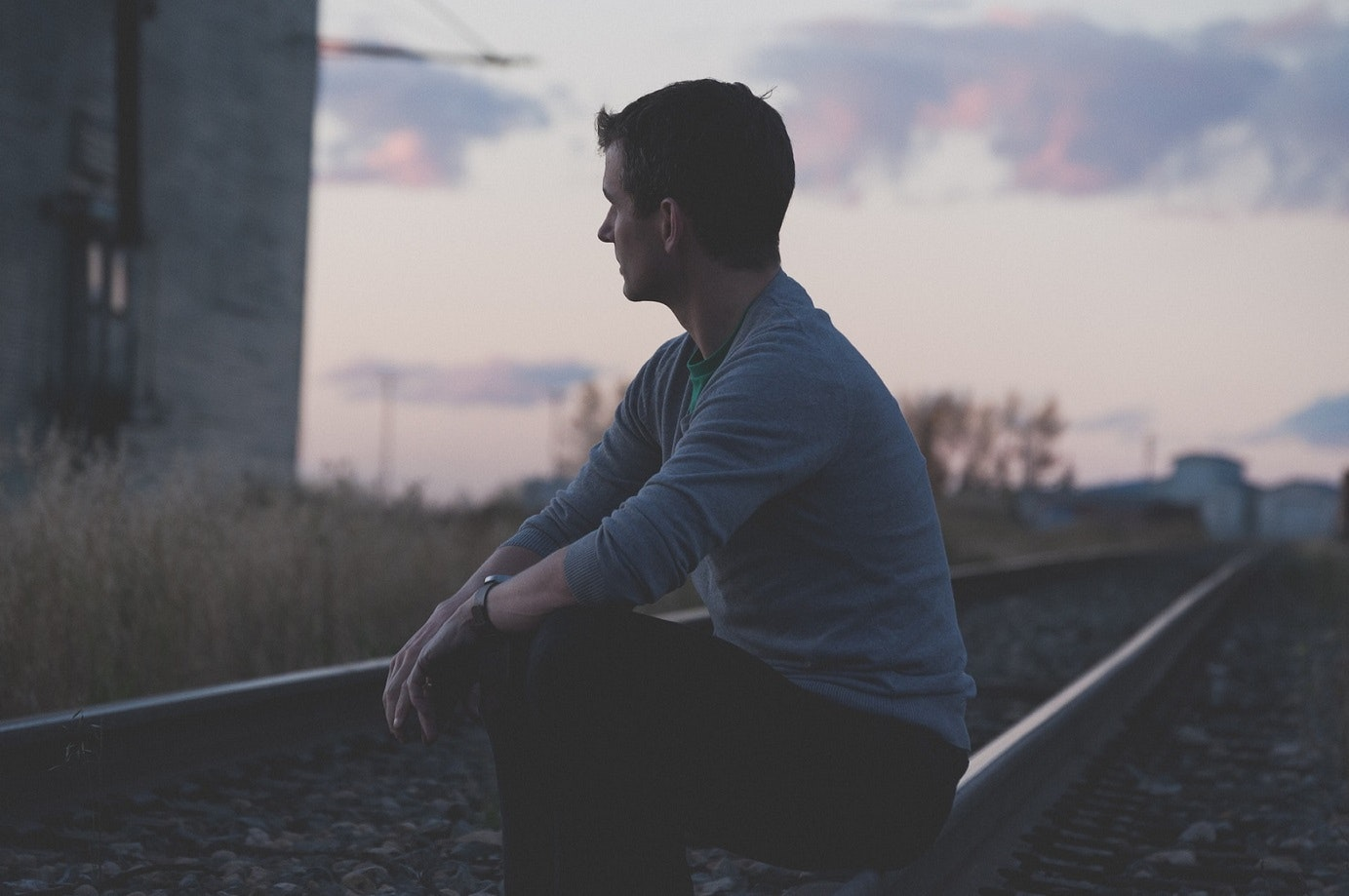 man sitting on a train track