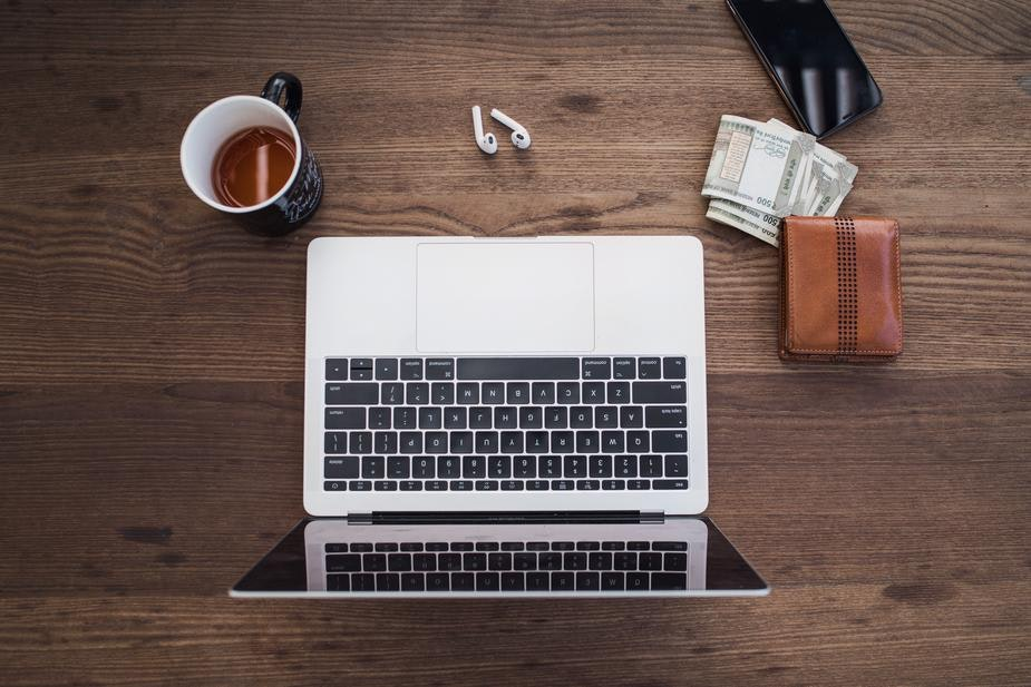 An overhead shot of an open laptop, coffee and wallet