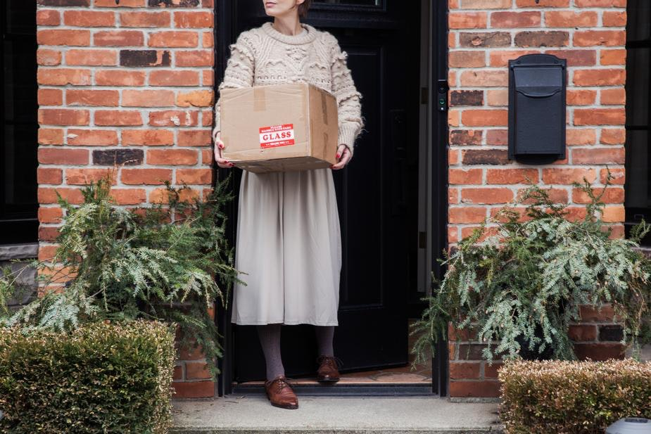 A woman collects a package from her doorstep
