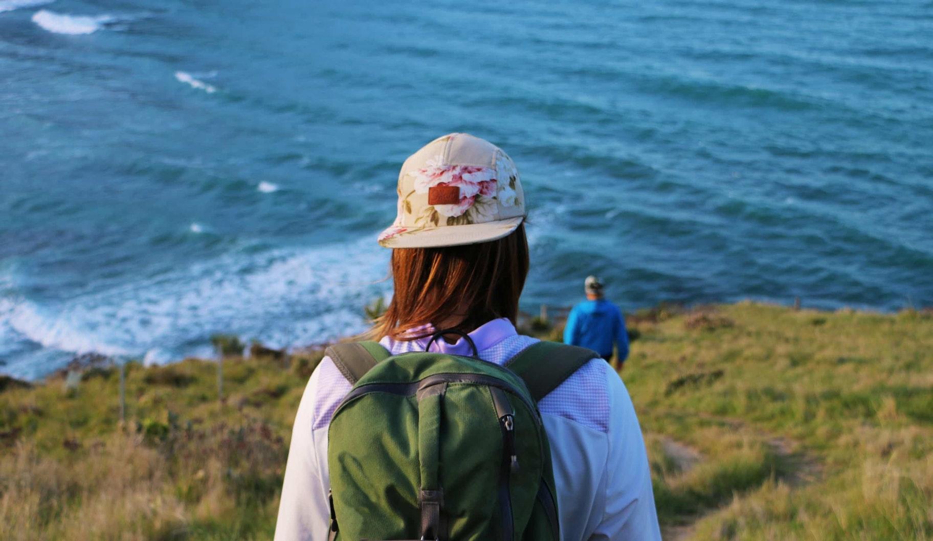 Woman wearing an Offcut hat walks towards the ocean