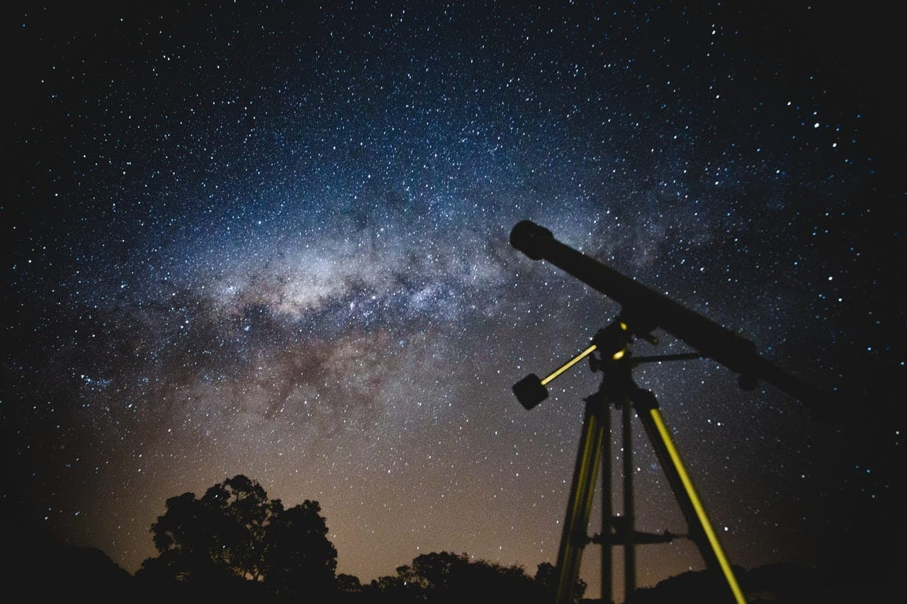 photo of the night sky and a telescope