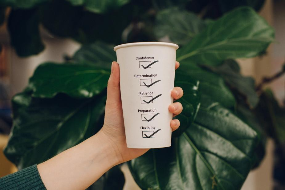 hand holding a paper cup with a motivational checklist on it
