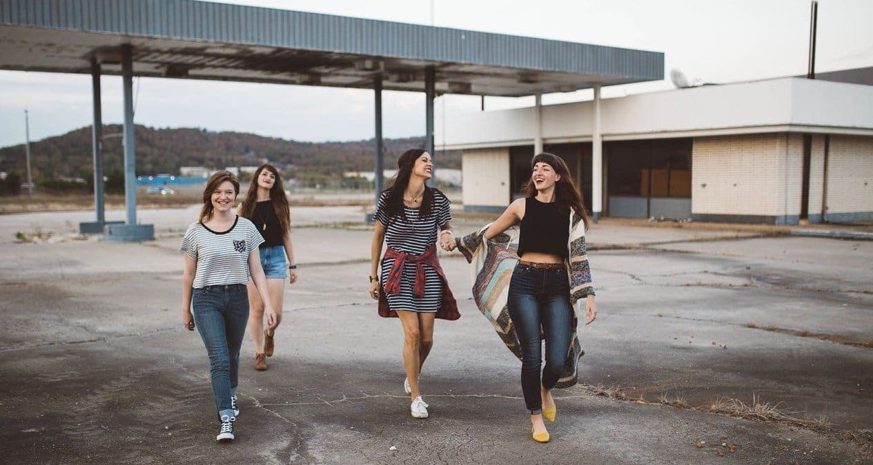 four teenage girls walk towards the camera smiling