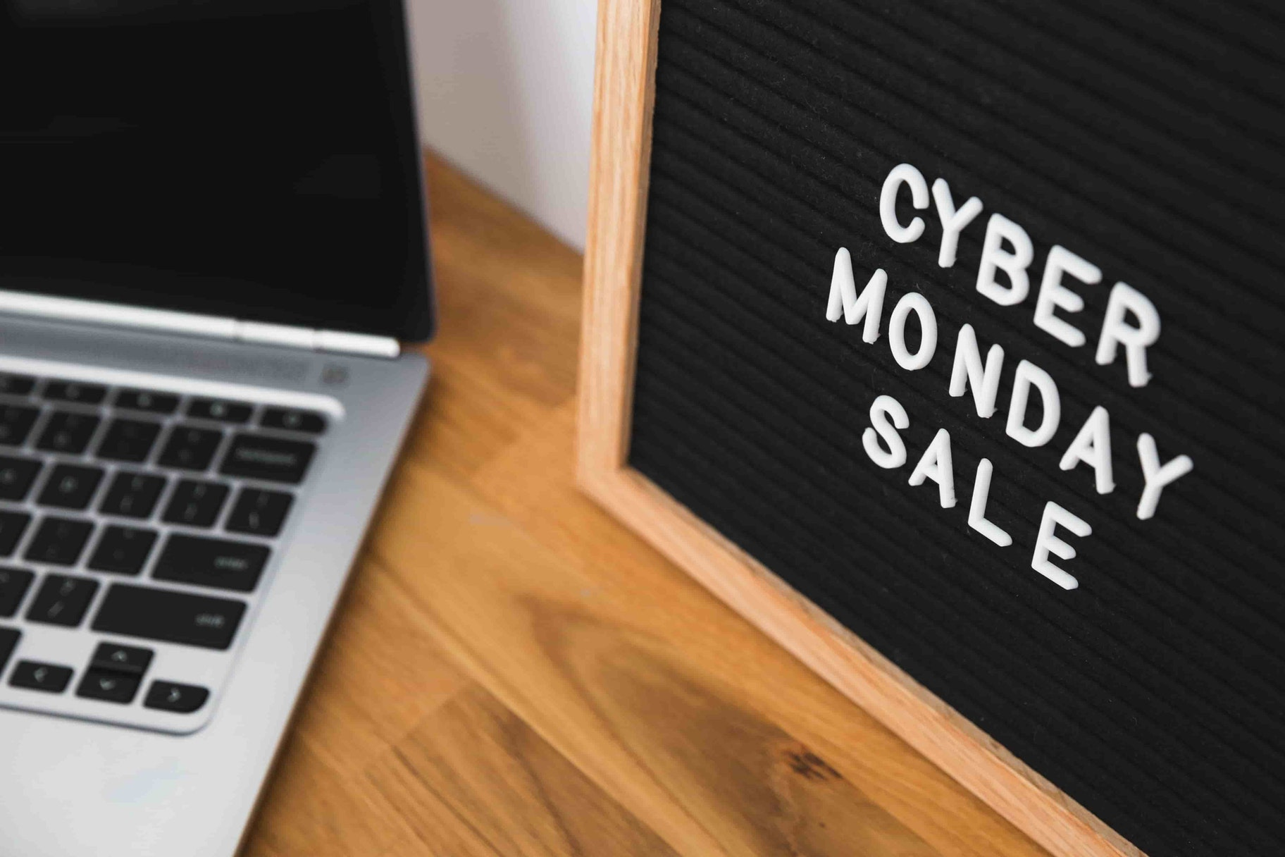 A letterboard with 'cyber monday sale' sits next to an open laptop