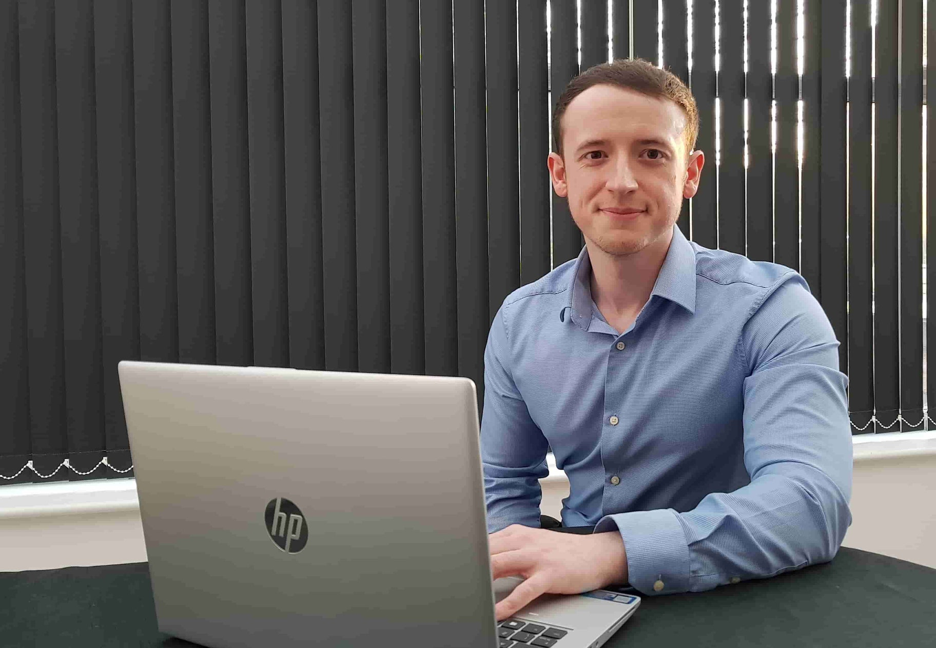 Chris Wane sits behind HP laptop