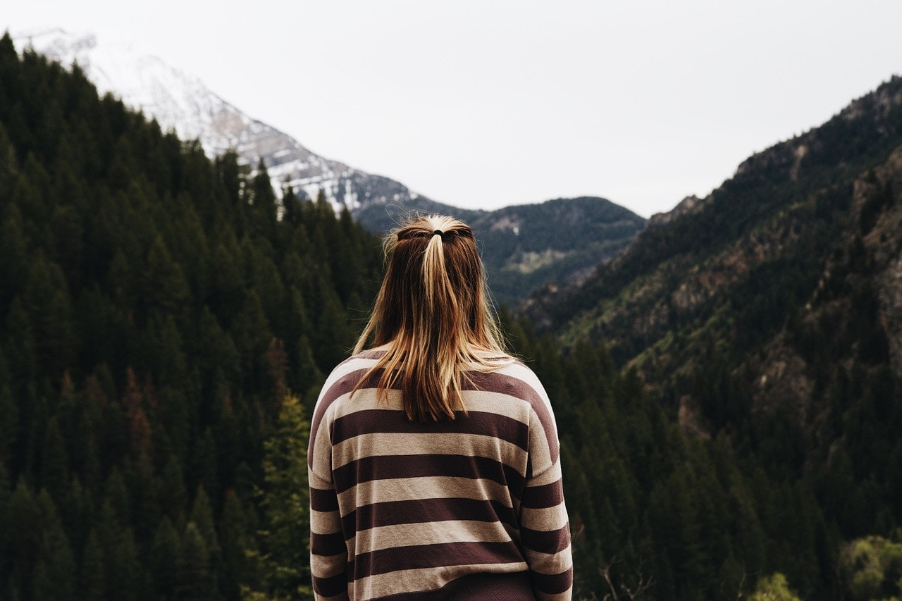Woman in a striped jumper faces toward mountains