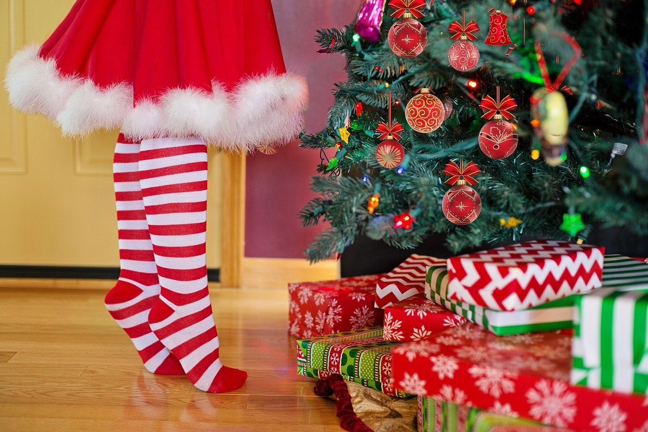 A child wearing stripey socks stands near a christmas tree with presents