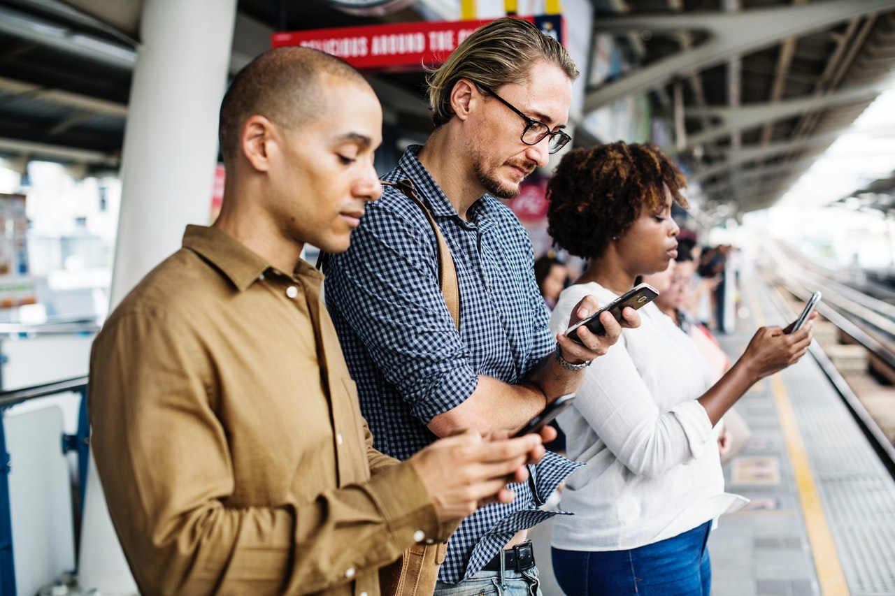 A diverse group of people standing on train platform all checking smartphones