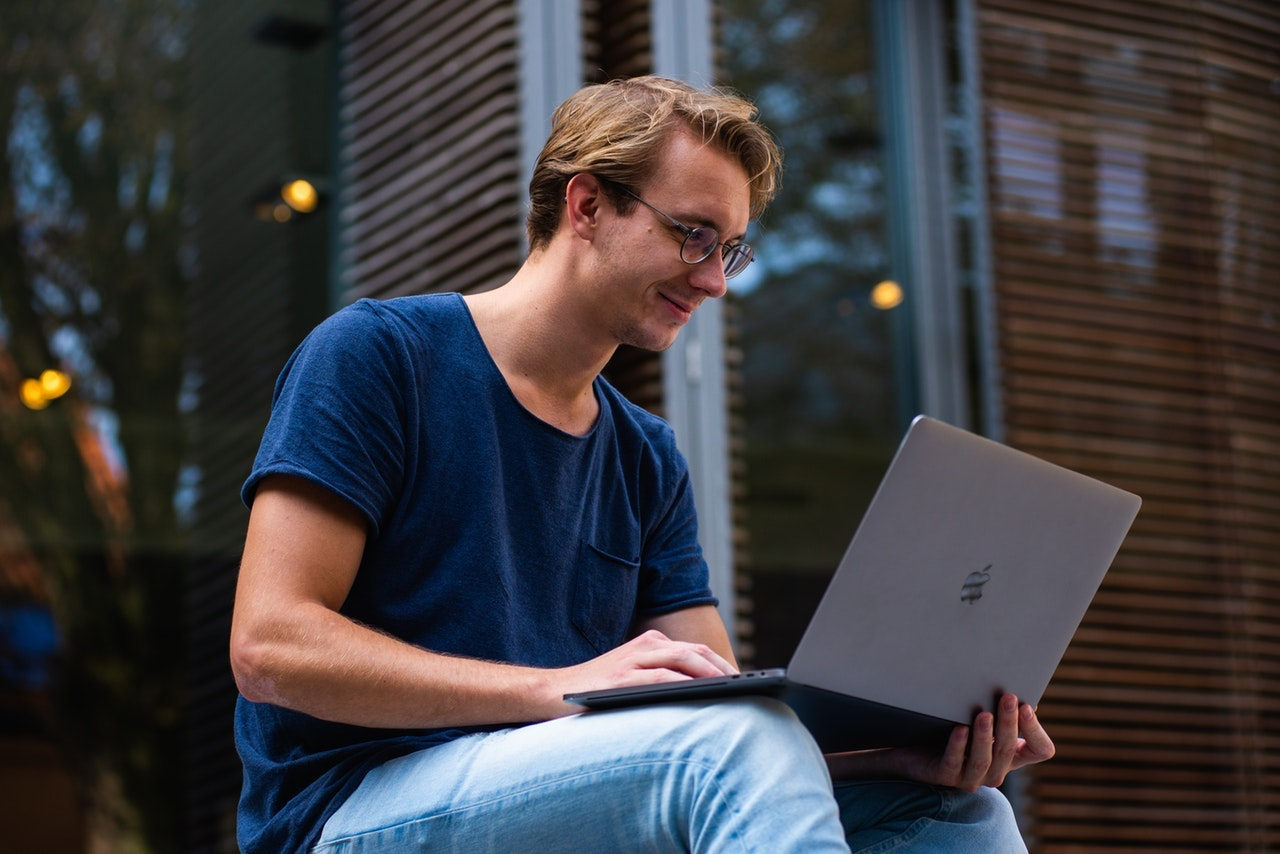 A young man wearing jeans and a tshirt uses his Apple computer outside