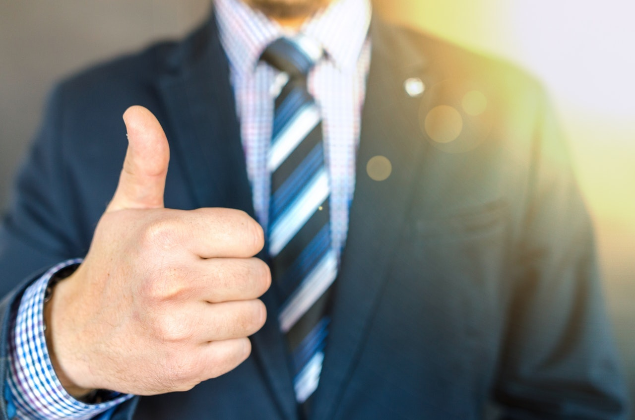 Torso of a man in a suit giving a thumbs up sign