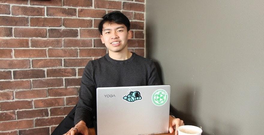 Yuanda Wang sitting behind a laptop against a brick wall