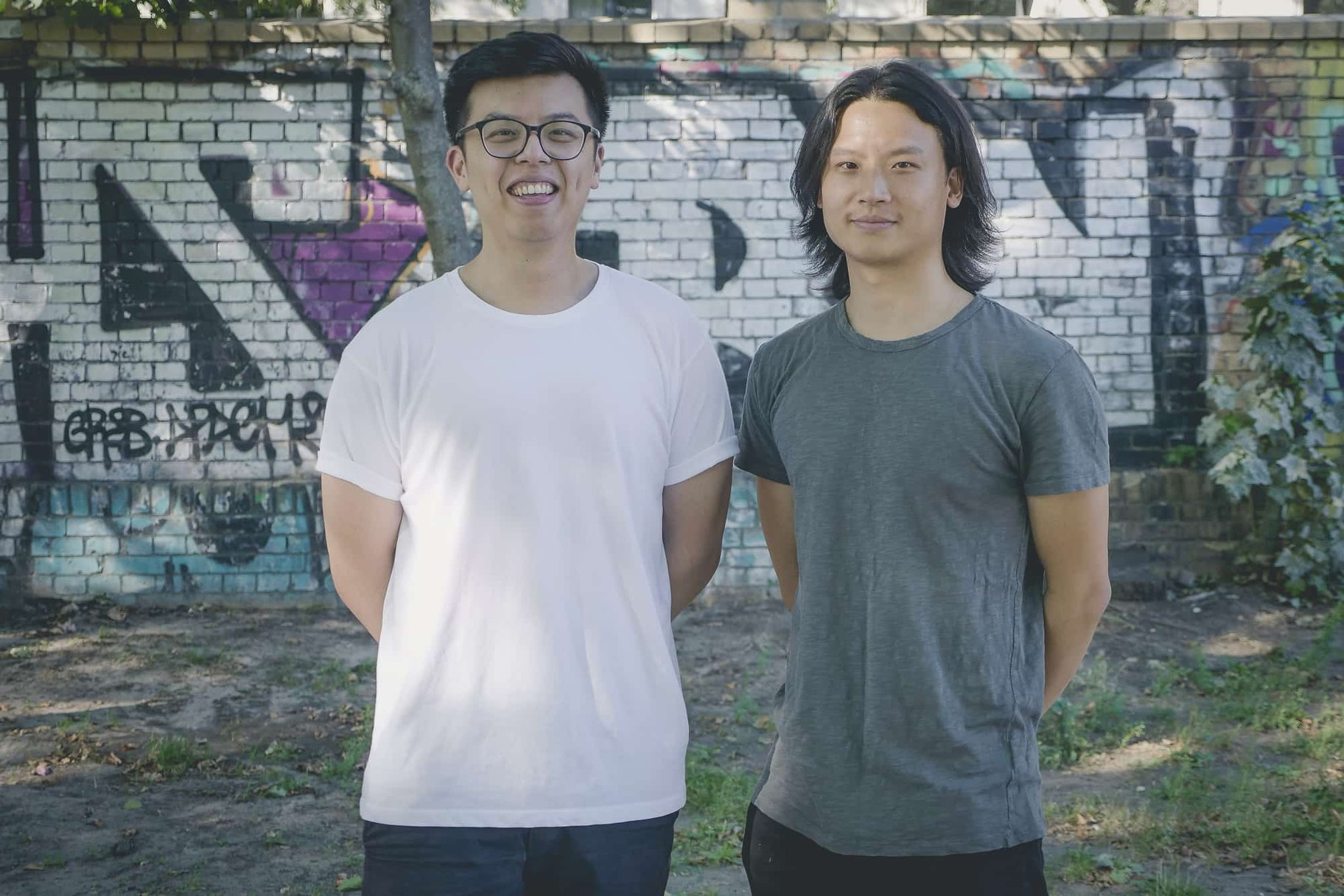 Jacky and Albert stand against a graffiti'd brick wall