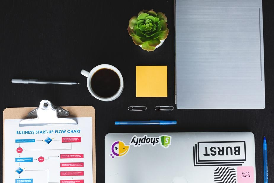 An above shot of a laptop and coffee