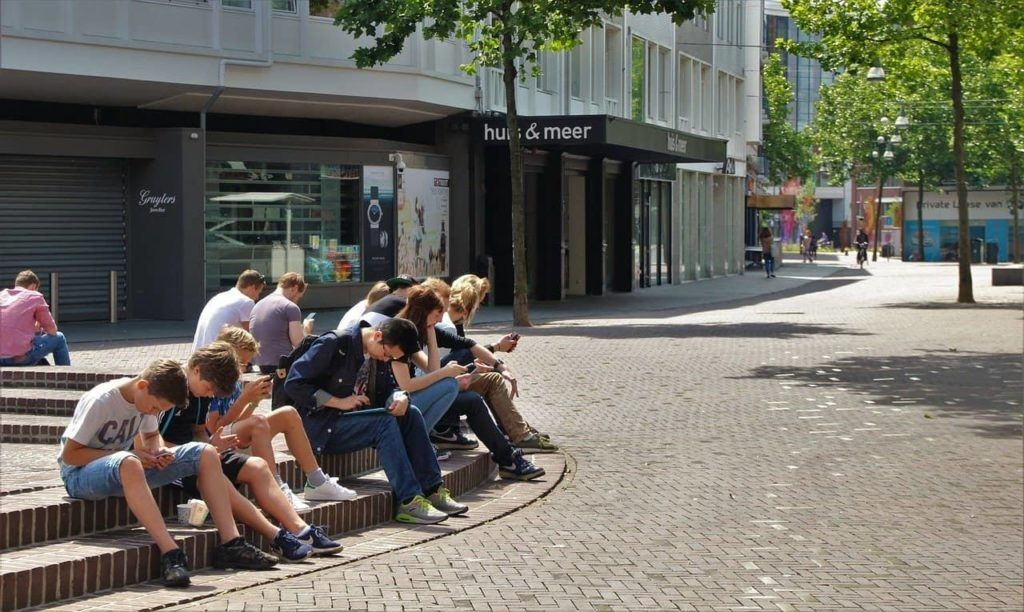 a bunch of teenagers sit on a street all looking at their phones
