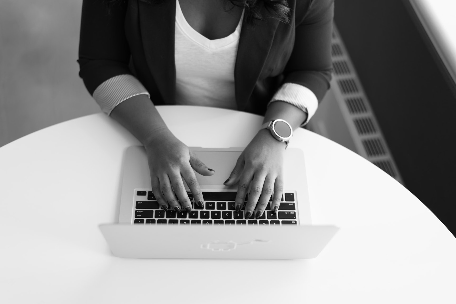 black and white image of woman using laptop