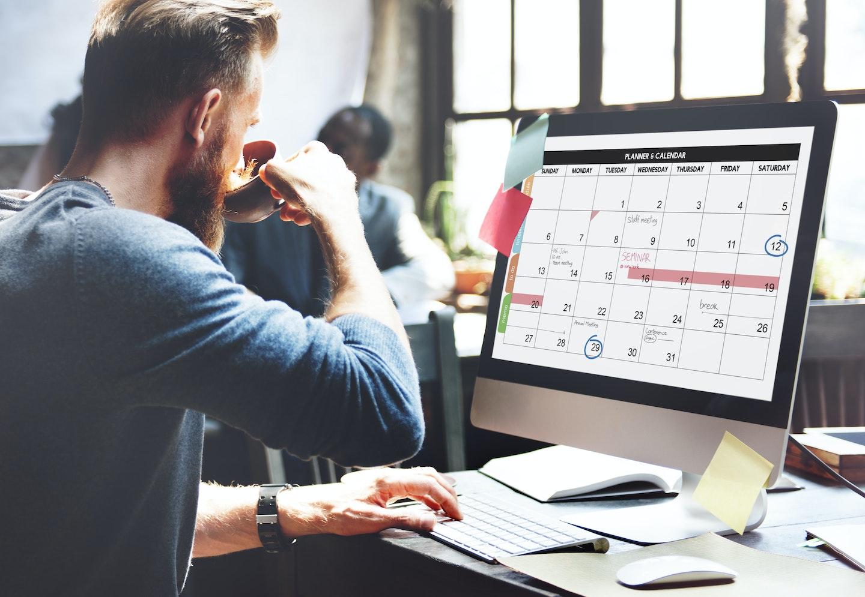 homem organizando calendário em computador