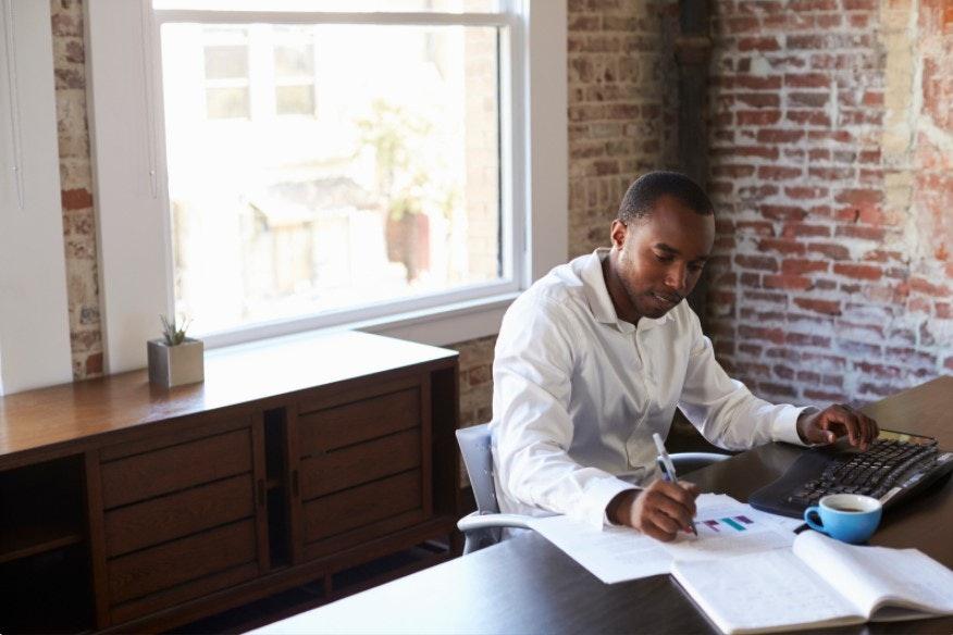 homem trabalhando em gráficos em sua mesa