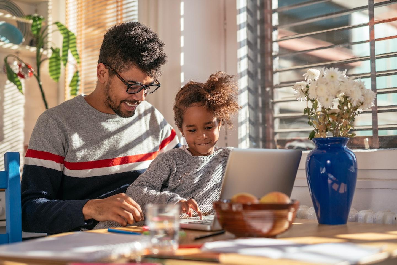 pai e filha usando laptop em casa