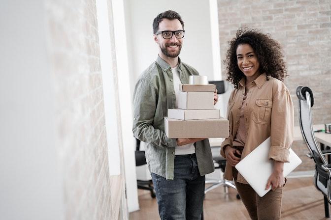 homem e mulher em escritório, segurando materiais