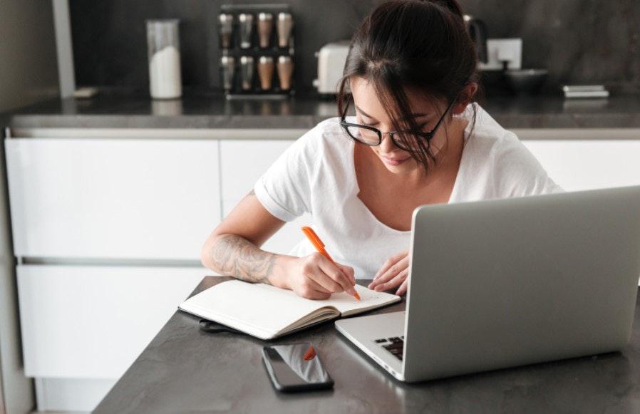 mulher escrevendo em caderno em frente a um notebook
