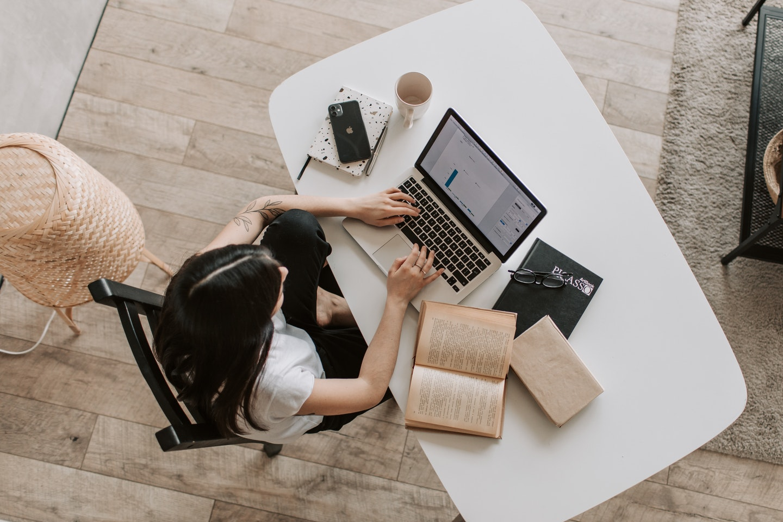profissional trabalho em computador, com livros abertos