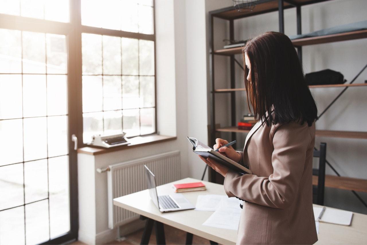 Use uma agenda para sua gestão de tempo: empreendedora escrevendo em agenda