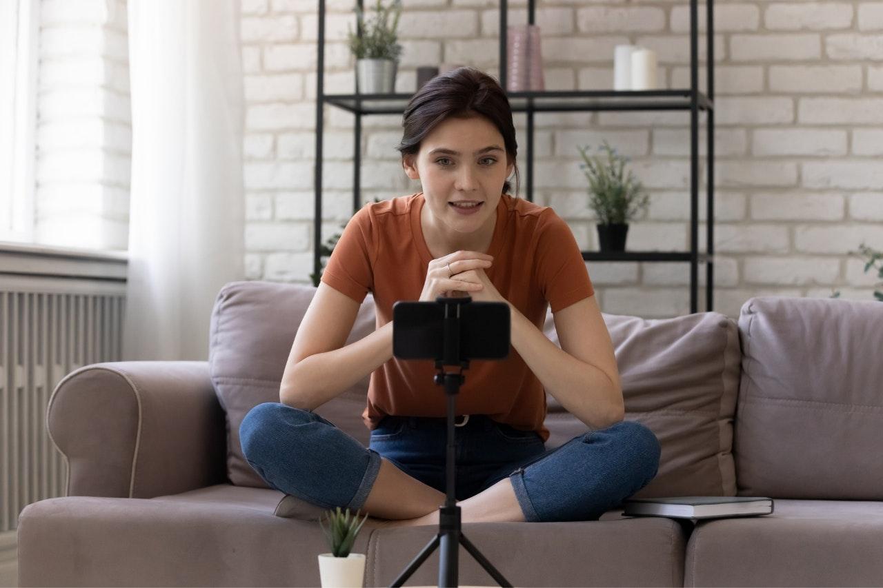mulher sentada em sofá, utilizando o Facebook Live