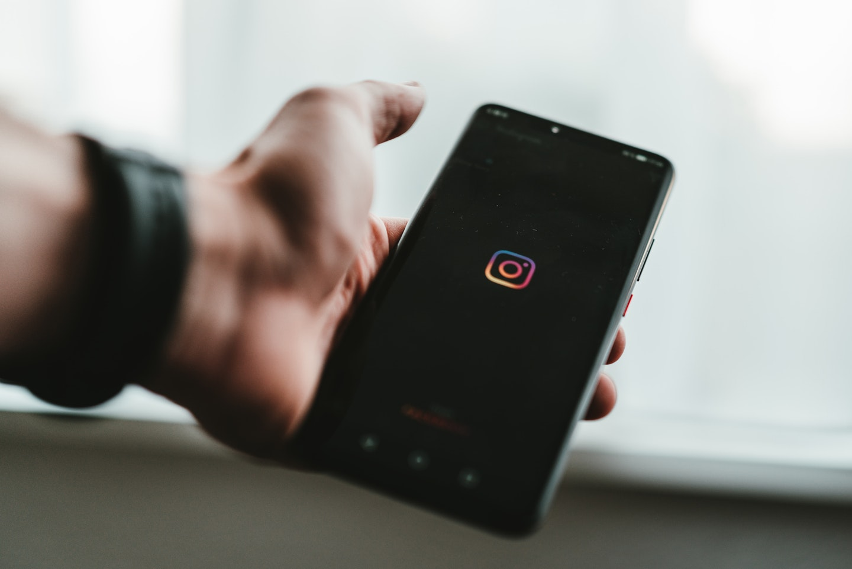 Instagram comercial: como criar anúncios com o Instagram Ads. Homem segurando celular com tela do Instagram